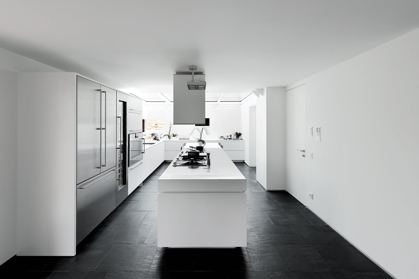"""""""We wanted a big kitchen to live in, not a small technical place to cook,"""" says Guido Chiavelli, who returns from work every day to have lunch with his wife and son. At the far end, a glass ceiling presents an open-air feeling. """"Cooking while it's raining is fascinating,"""" he says. Tagged: Kitchen, Dark Hardwood Floor, Refrigerator, and White Cabinet.  Cocina by Javier Rodríguez from A Renovated Farmhouse in Northern Italy"""