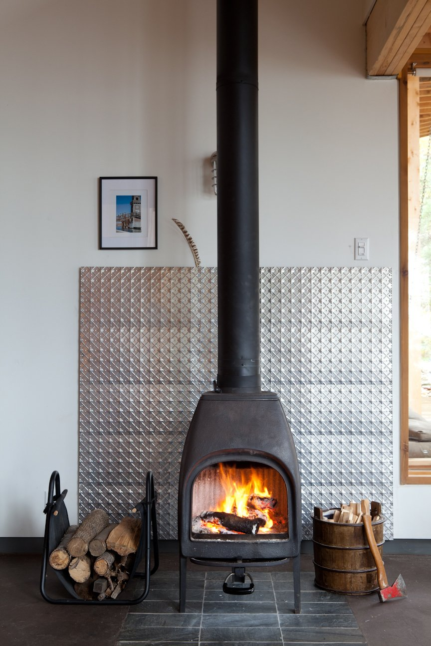 The structures share a solar panel, but the families control their own home's heat level with a wood-burning stove. Modern Wood-Burning Stoves by Megan Hamaker