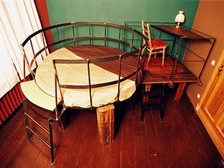 "Although you can't be over six feet tall to stay in this room, it is the most traditionally appealing. The bed and desk are built on top of a rustic ""table,"" but otherwise everything is right side up and won't trigger a panic attack.<br><br>For more information about the hotel, visit <br><br>propeller-island.de."