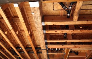 The ceiling in the living room shows the network of plumbing. Small copper pipes carry water and the black cast iron pipes carry waste. Plumbers and electricians drill through freshly installed studs and beams as they find a route for their pipes, conduits, and wires. Engineering calculations are used to locate areas where holes through the beams will have minimal structural impact.