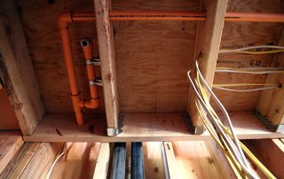 The orange CPVC pipes are for fire sprinklers. Since January 1st, 2011, fire sprinklers have been required in all new homes in California, adding a significant line item to the construction budget for a home.