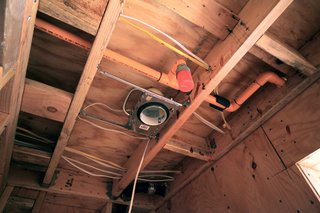 This ceiling image shows a full array of infrastructure; electrical wiring, orange fire sprinkler pipes, black cast iron plumbing, and also a recessed light housing from Lumens.com.