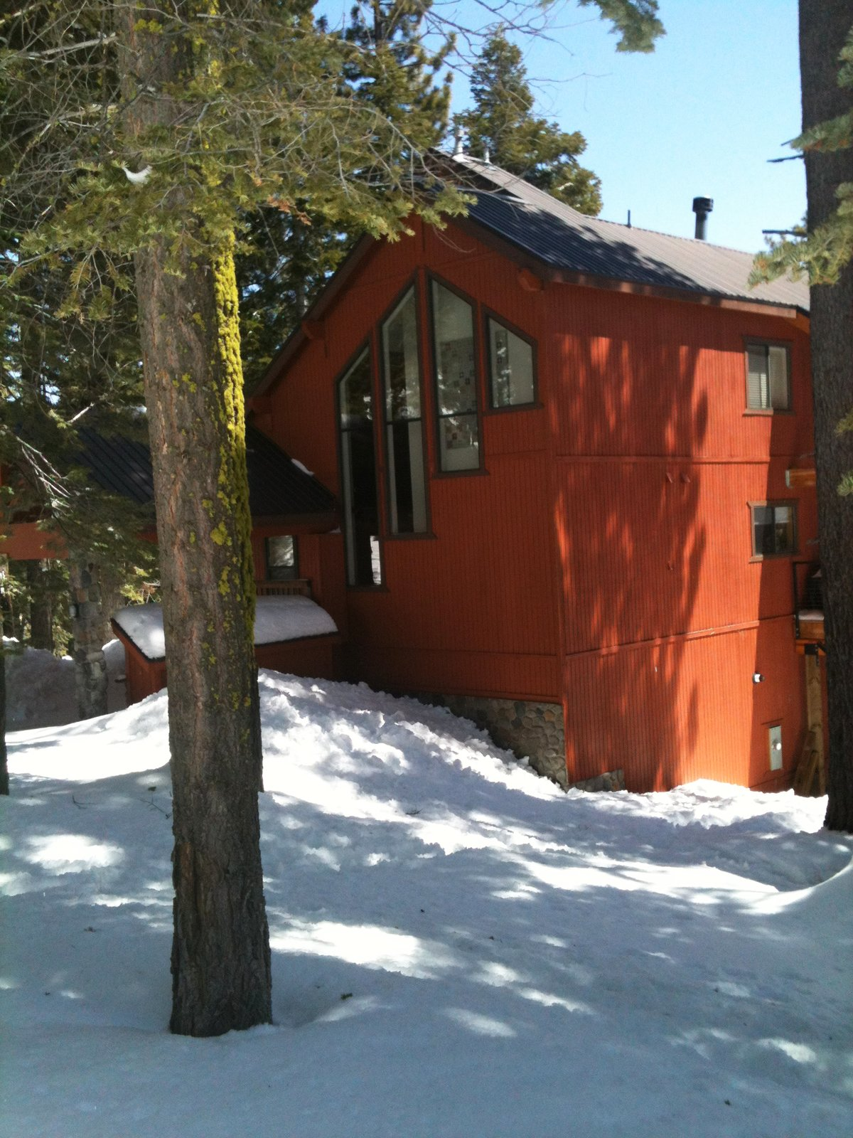 Amidst the brown natural tones of the surrounding cabins, this orange-red exterior pops. The contrasting charcoal trim and coordinated art in the window pull the whole thing together.  Cabin by kassidydavies@gmail.com from Snow in Bear Valley