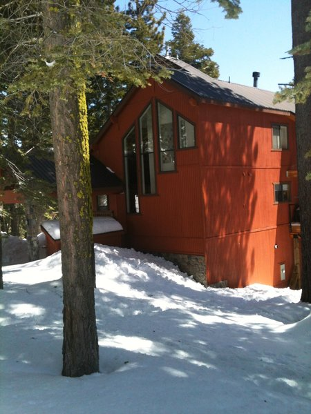 Amidst the brown natural tones of the surrounding cabins, this orange-red exterior pops. The contrasting charcoal trim and coordinated art in the window pull the whole thing together.