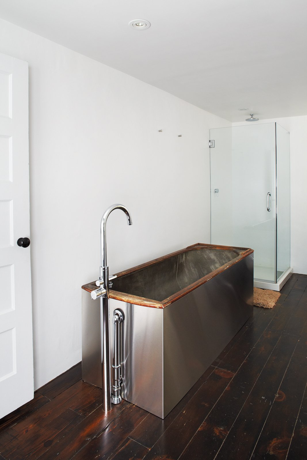 A salvaged 19th-century soaking tub wrapped   in stainless steel is topped by Hudson Reed faucets. Hope Floats - Photo 4 of 12