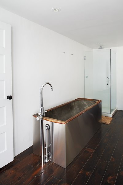 A salvaged 19th-century soaking tub wrapped   in stainless steel is topped by Hudson Reed faucets.
