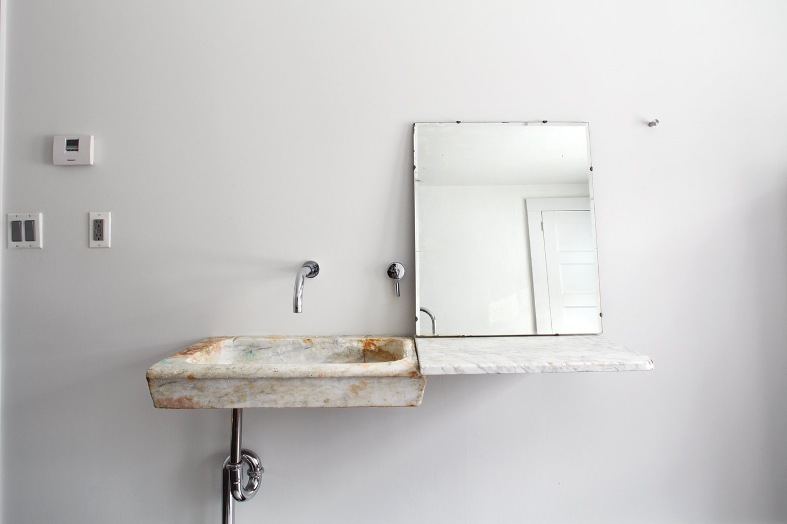 In the guest bathroom, Givone installed a hand-chiseled sink made of 17th-century marble quarried from the hills outside of Rome. Tagged: Bath Room, Wall Mount Sink, and Marble Counter.  Photo 10 of 12 in Hope Floats