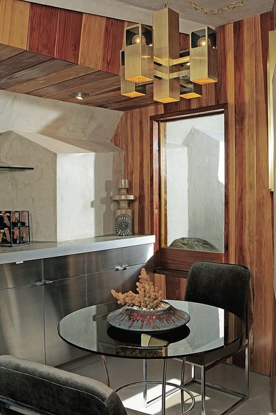 The eat-in kitchen features poured-in-place concrete countertops and redwood wall paneling.