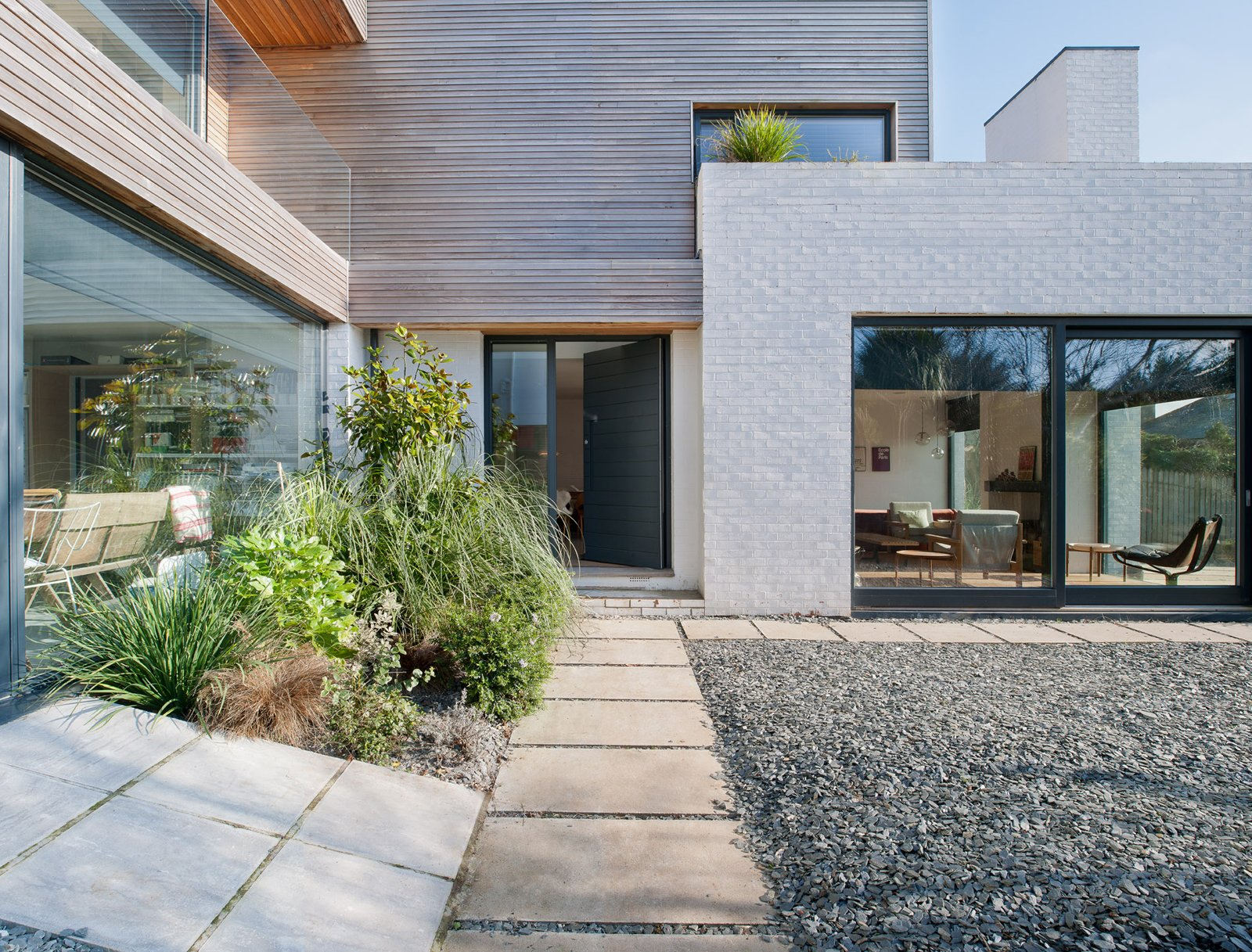 A path leads past glazing and gravel to the front door. Tagged: Outdoor, Pavers Patio, Porch, Deck, Stone Patio, Porch, Deck, and Front Yard.  Photo 10 of 18 in An Obsessed Designer Fills Her Home with Vintage Finds
