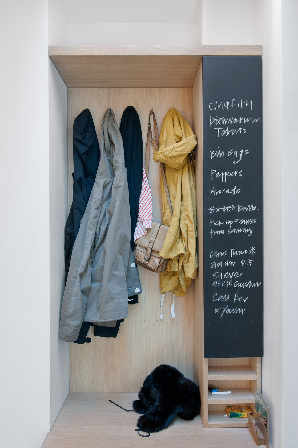 A built-in closet and chalkboard surface in the entry keeps things tidy and the couple's to-do list in order.  Photo 15 of 18 in An Obsessed Designer Fills Her Home with Vintage Finds
