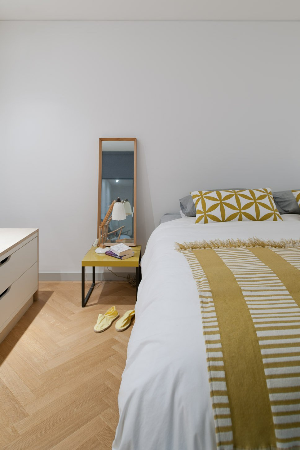 A peek inside the master bedroom, with touches of marigold yellow throughout. Tagged: Bedroom, Bed, Table Lighting, and Light Hardwood Floor.  Photo 16 of 18 in An Obsessed Designer Fills Her Home with Vintage Finds