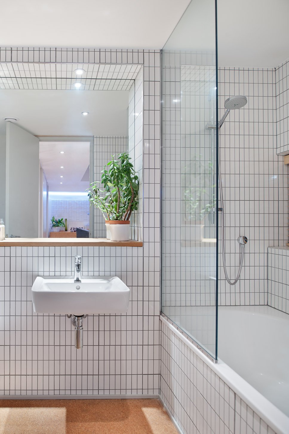 """I put everything that I've always loved into this house,"" says Tyler—and that includes white tiles edged with gray grout in the bathroom, a design move previous clients had balked at. Tagged: Bath Room, Drop In Tub, and Wall Mount Sink.  Photo 17 of 18 in An Obsessed Designer Fills Her Home with Vintage Finds"