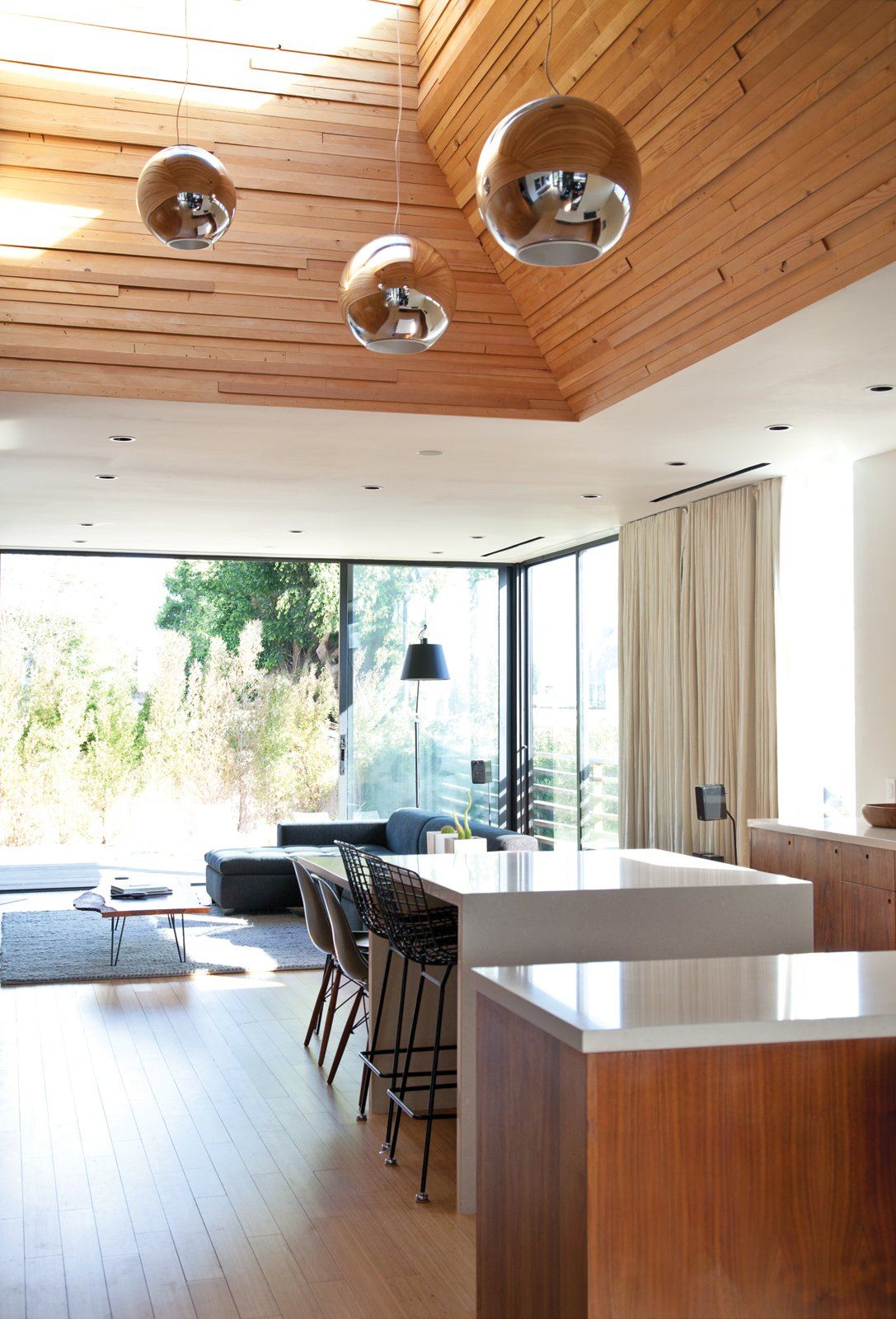 "The Globo di Luce pendants in the kitchen are by Roberto Menghi for Fontana Arte. Tagged: Dining Room and Chair.  Photo 8 of 9 in You Won't Be Calling This House a ""Man Cave"""