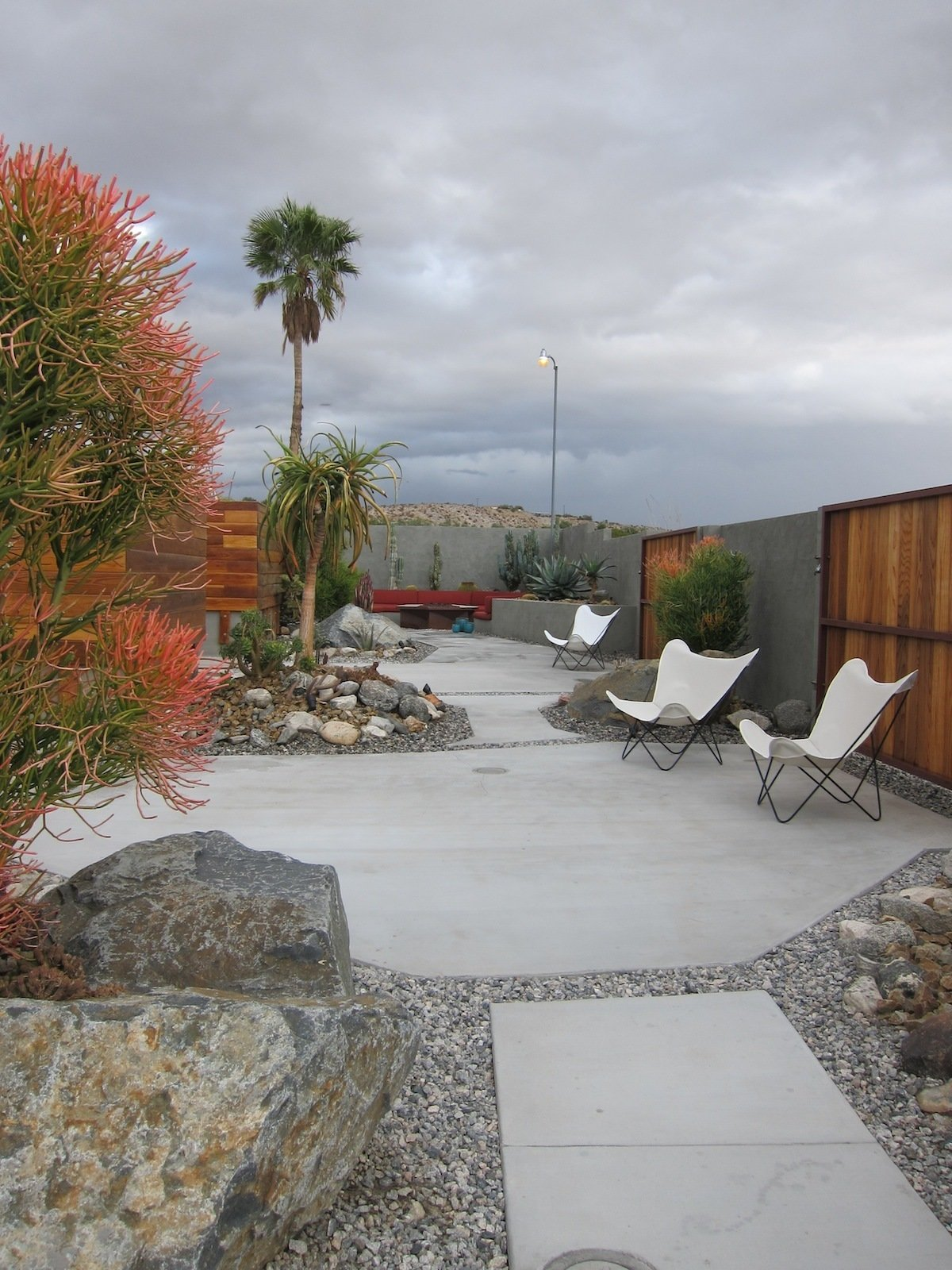 On the other side of the fence—built to protect the property from flash floods—is a desert oasis with cactus-lined walkways and patios set with butterfly chairs.  Photo 4 of 6 in The Midcentury Architecture of California Modernist John Lautner