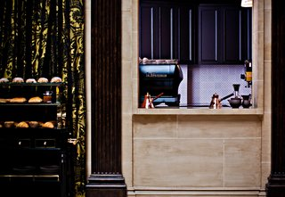 The NoMad Hotel, New York - Photo 3 of 12 - Even in the kitchen to dining room passthrough, the details are just right: a La Marzocco espresso machine and a peek of vibrant purple set inside a travertine windowbox.