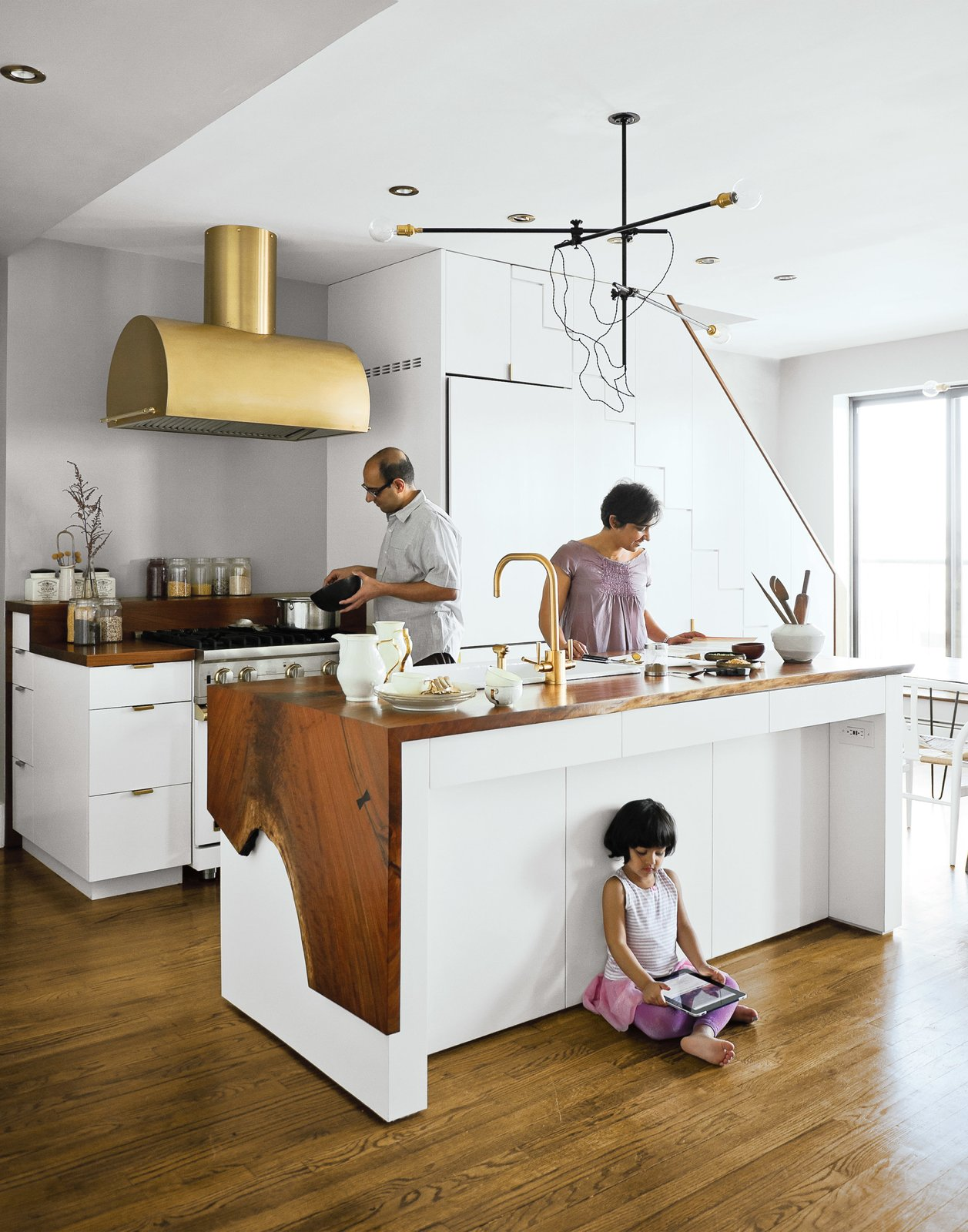 The Mandayam–Vohra family gathers under one of Workstead's signature three-arm chandeliers, shown here in its horizontal configuration. Tagged: Kitchen, White Cabinet, Medium Hardwood Floor, Wood Counter, Metal Backsplashe, and Pendant Lighting.  Small Spaces with Incredible Kitchens by Robert Gordon-Fogelson from A Minimal Yet Mighty Brooklyn Apartment