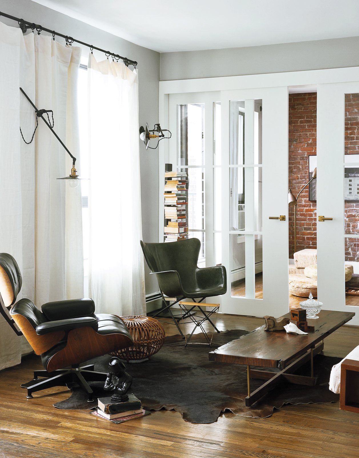 In the living room, an Eames lounge chair   is matched with a Richard Conover–designed fiberglass chair in similar proportions. A custom coffee table by Asher Israelow com-plements the industrial lighting by Workstead, affixed to walls painted in Farrow and Ball's Manor House Gray. The sliding doors leading into the home office were fabricated by Markus Bartenschlager. Tagged: Living Room, Recliner, Coffee Tables, Chair, Bookcase, Wall Lighting, Rug Floor, and Dark Hardwood Floor.  Photo 8 of 19 in How to Take a Dwell Photo