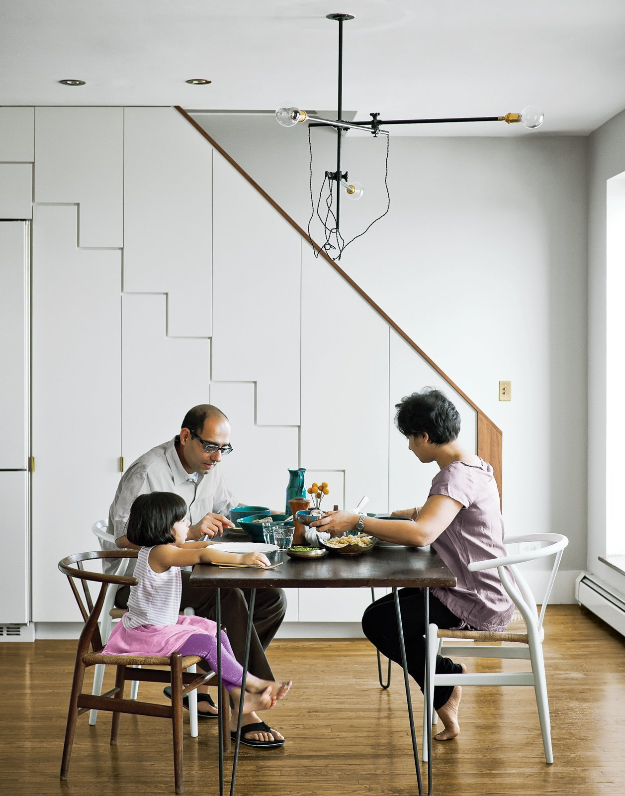 At right, the family dines at a mid-century walnut table found on eBay,   seated at a mix of new and antique   Wishbone chairs by Hans Wegner.  In the Home by Carl Hansen & Son from A Minimal Yet Mighty Brooklyn Apartment