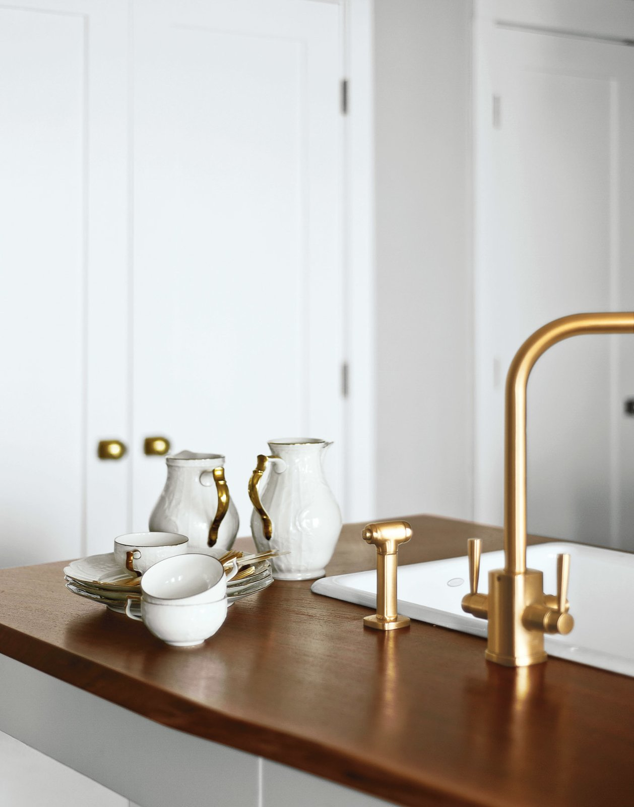 A Rohl faucet was stripped and replated in brushed brass. The modern fixtures prove a lovely contrast to the American walnut countertops and original Rosenthal dishware.  Photo 10 of 12 in A Minimal Yet Mighty Brooklyn Apartment