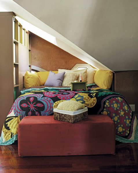 This top floor loft space in Atlanta has uneven ceilings and no walls, so Schuneman sectioned off a nook for her bed using a tall bookcase. Reprinted from The First Apartment Book by Kyle Schuneman. Copyright © 2012.  Published by Clarkson Potter, a division of Random House, Inc.