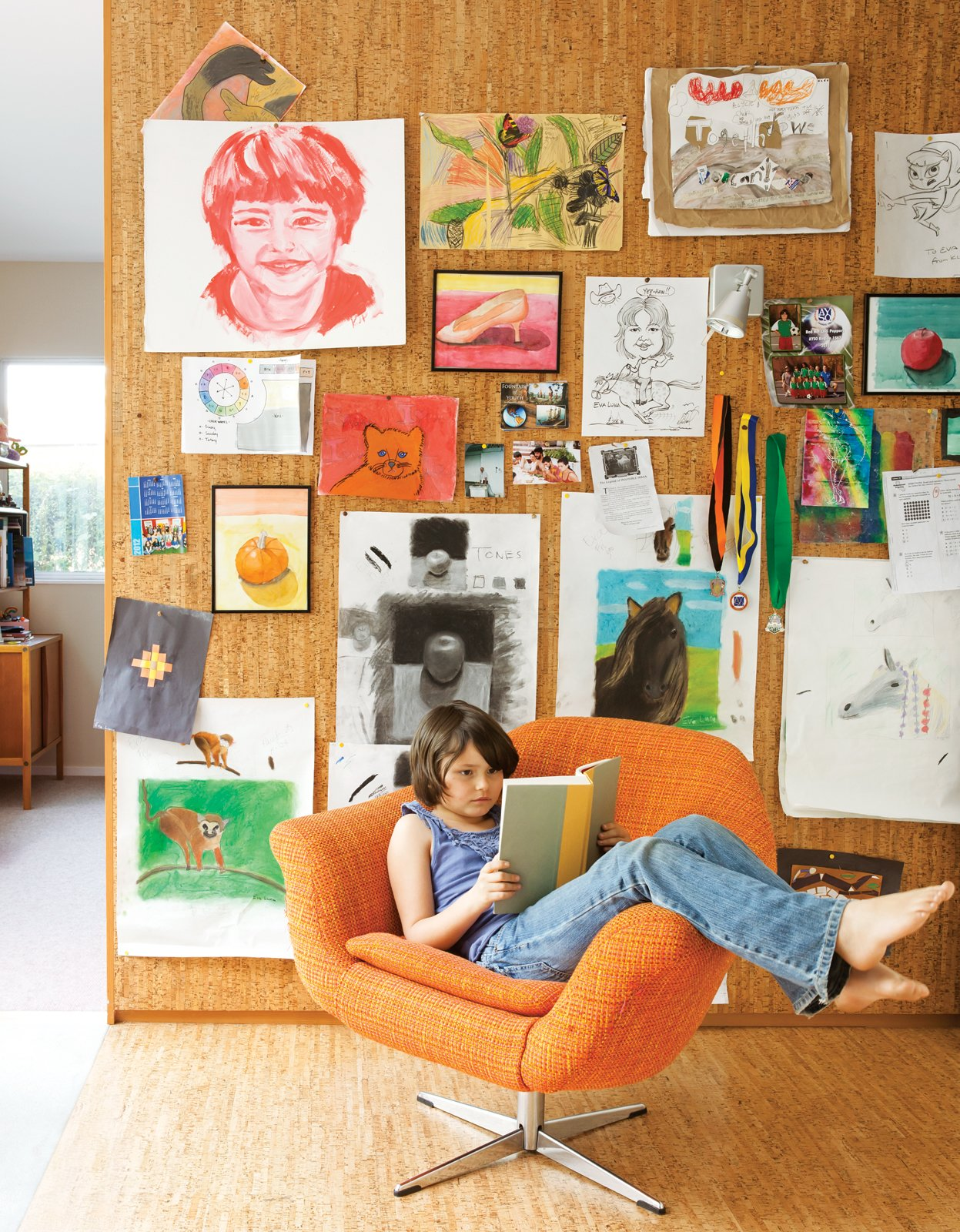 The pair's art covers a cork wall where Eva Luna reads in a vintage Danish lounge chair. Tagged: Living Room, Chair, and Light Hardwood Floor.  Photo 4 of 13 in A Fresh Dose of Color Livens Up This Midcentury Los Angeles Home