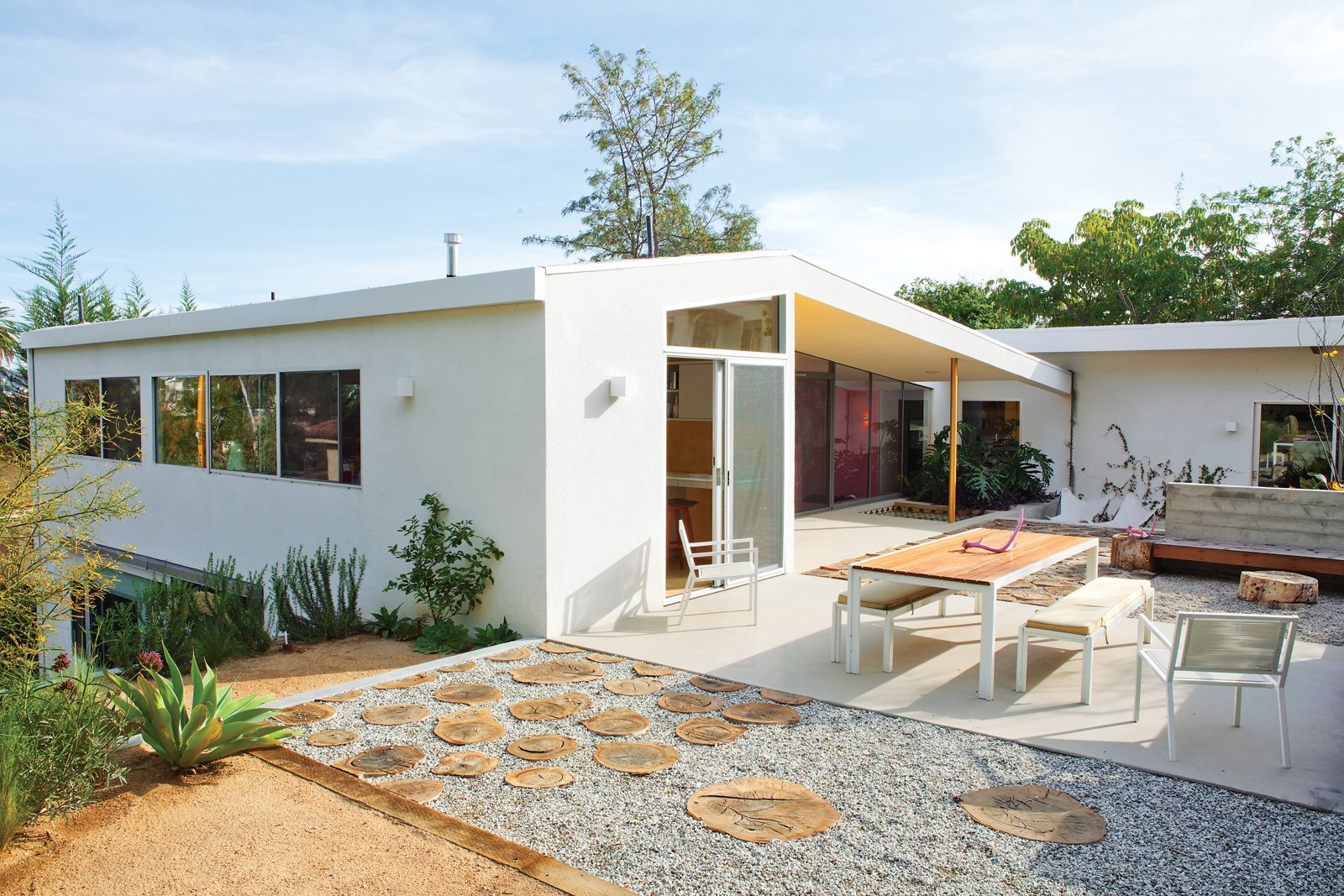 Some 35 percent of the materials from the renovation were resurrected in the yard: Redwood panels became fencing. Blocks cut from original concrete patios form the snake wall. And Purdy plans to crochet colorful cozies over various branches and stumps.  Photo 12 of 13 in A Fresh Dose of Color Livens Up This Midcentury Los Angeles Home