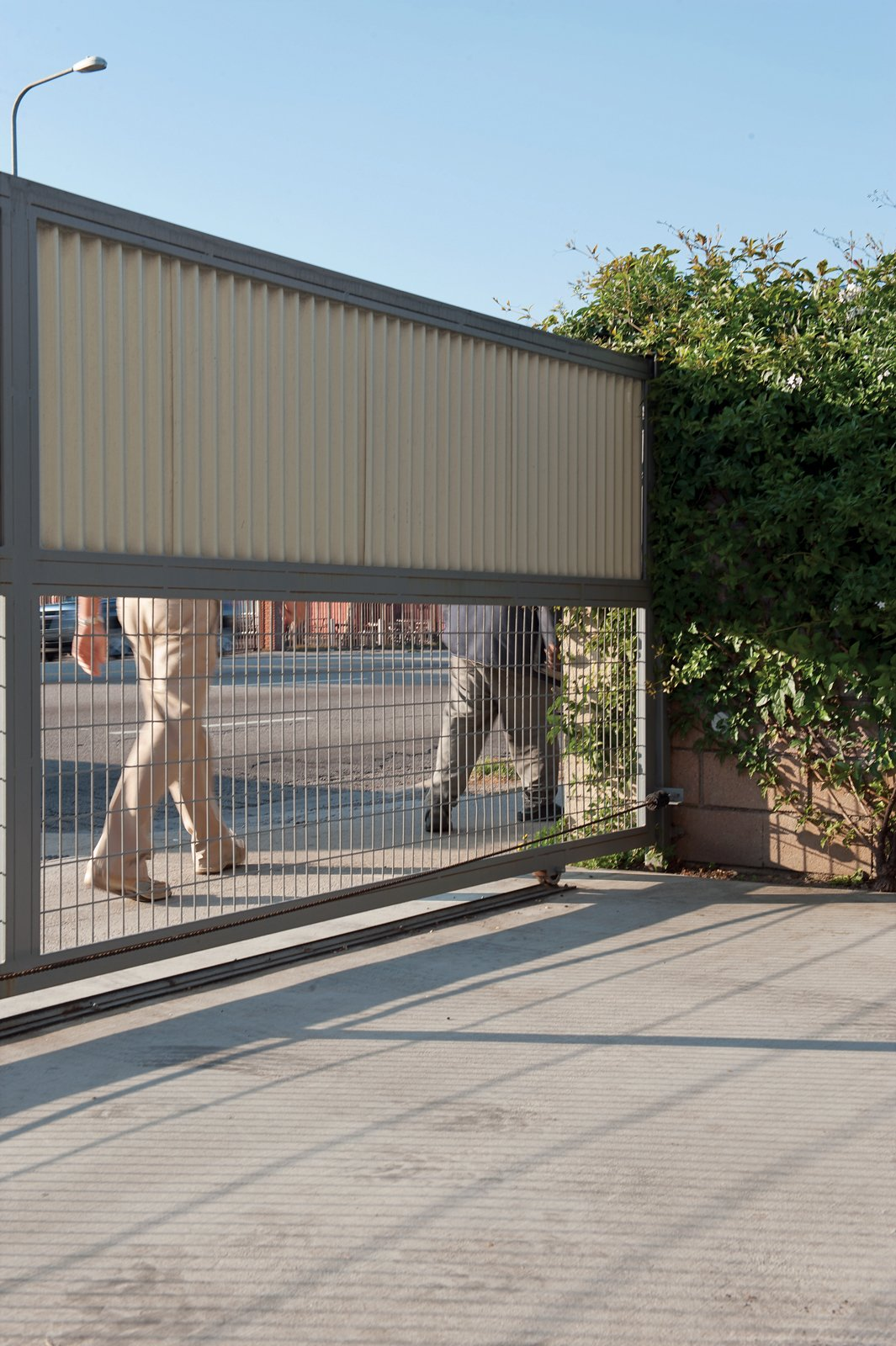 Playing Defense  Cooper was faced with a conundrum when designing her property gate. She didn't want passersby to be able to see in, but neither did she want a totally solid barrier keeping street life out. Using spare sheet metal, she fashioned a gate that's solid on top and porous steel wire on the bottom. With a tube steel structure for support and a DoorKing 9100 motor to open and close the heavy fence, she was set.   doorking.com  Photo 11 of 13 in 131-Day House