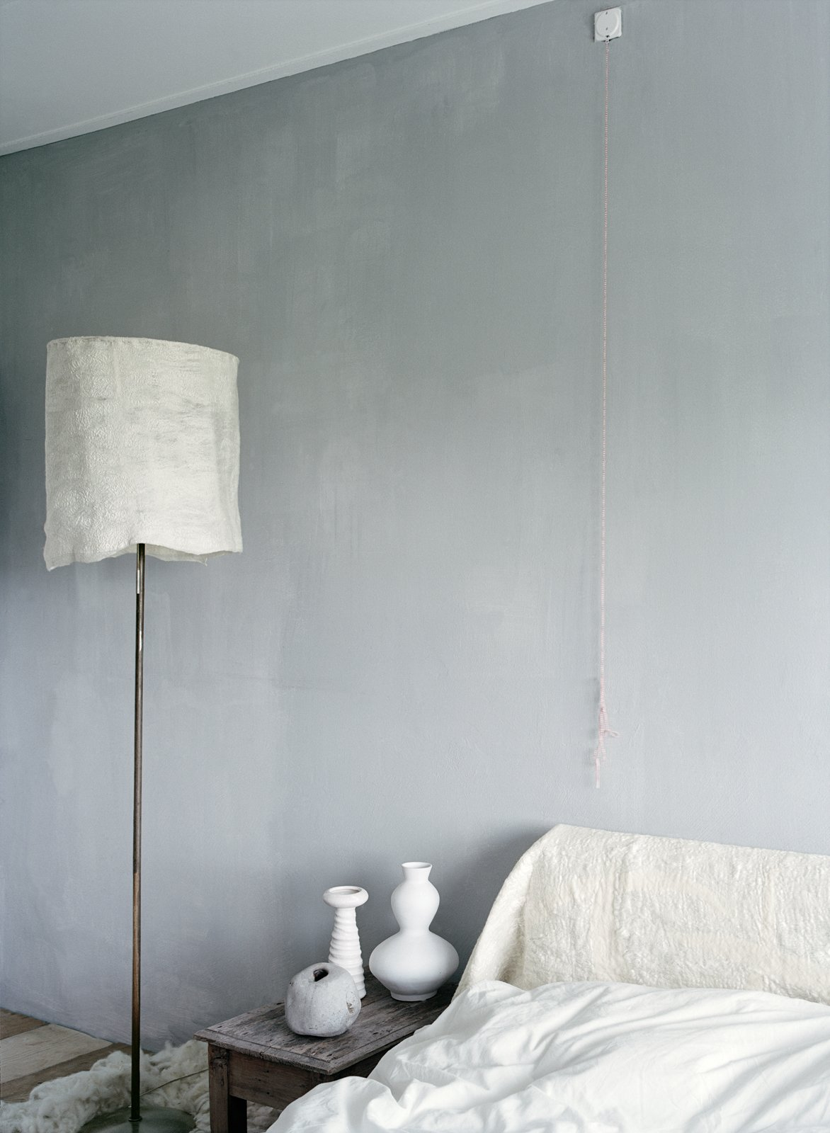 The couple's bedroom is a serene space with tinted plaster walls and a white felt headboard and lampshade by Leen.