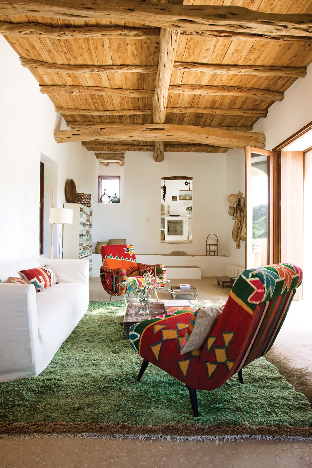 In Marquina and Font's living room, a pair of kilim-covered chairs by Philippe Xerri, a chest of drawers by Piet Hein Eek, and a handmade Tunisian rug provide bursts of color amidst the overall scheme of white, ecru, and cream. Tagged: Living Room, Chair, and Sofa.  Photo 4 of 9 in This Designer Escapes to Ibiza for Some Peace and Quiet