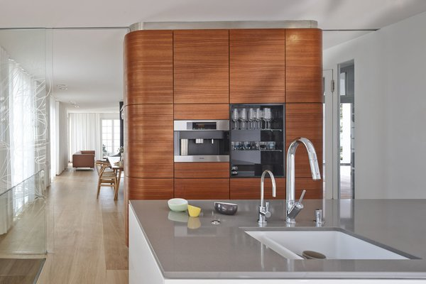 The kitchen features Miele and Bosch appliances surrounded by oak flooring from Bois Ditton; the shelves are walnut.
