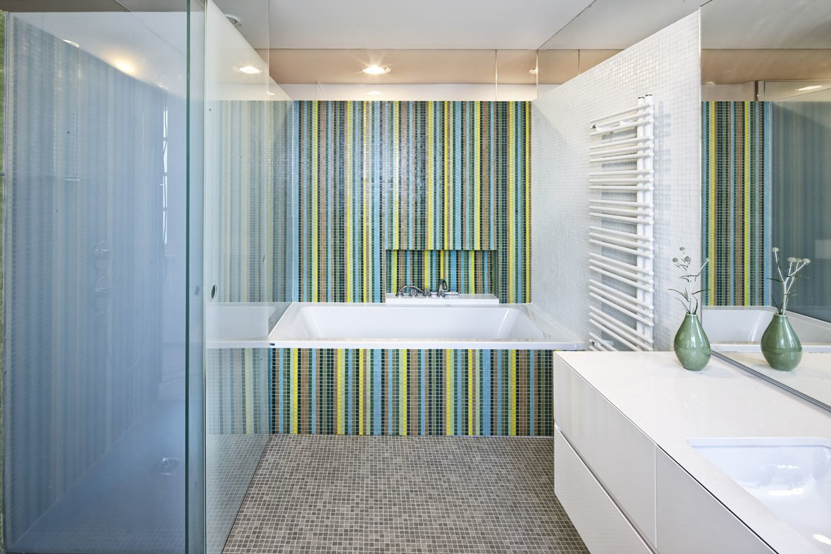 Glass elements not only allude to the ocean, but also lend a fresh look to some of the rooms. Here, Trend glass mosaic tiles brighten up the bathroom. Axor fixtures from Hansgrohe stand next to a minimalist radiator from Zehnder. Tagged: Bath Room, Drop In Tub, Mosaic Tile Wall, and Ceramic Tile Floor.  Best Photos from A Renovated Modernist Oasis in the French Riviera That Has Hosted Picasso and Royalty
