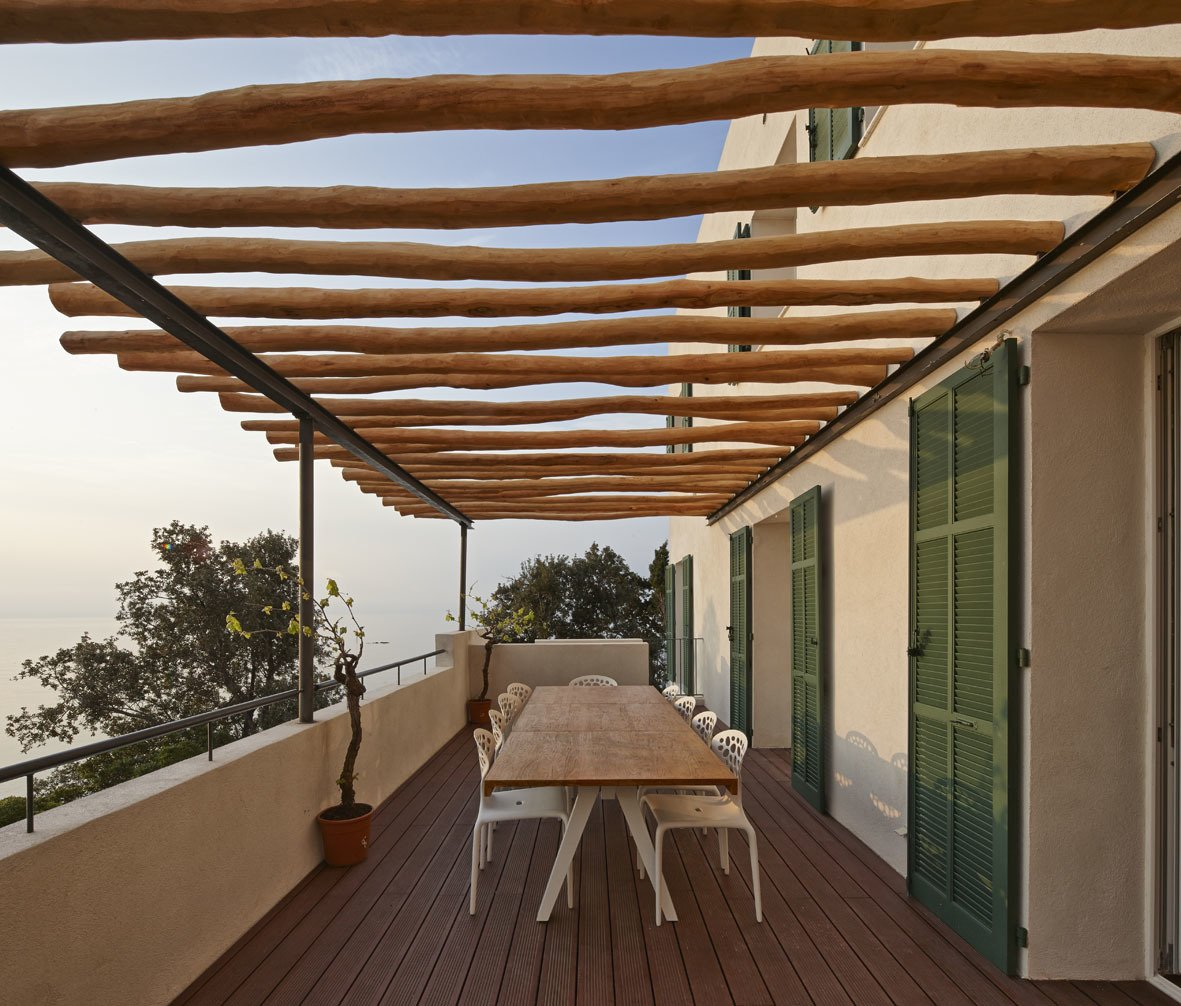 On the patio, robinia wood beams shade a Kettal Vieques dining table and set of Moroso Supernatural chairs. A Renovated Modernist Oasis in the French Riviera - Photo 7 of 9
