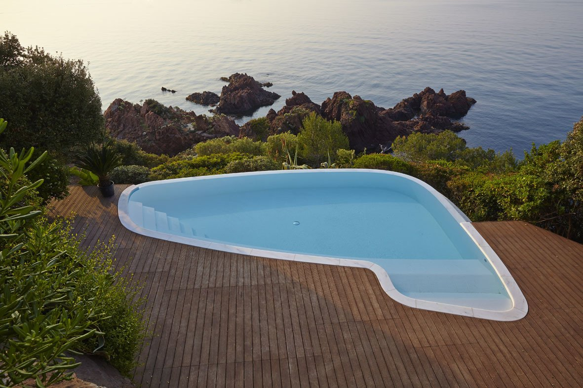The swimming pool was reshaped and refinished to blur the transition between deck and rocky outcrop. Beyond the pool is the villa's private beach, framed by lush vegetation.