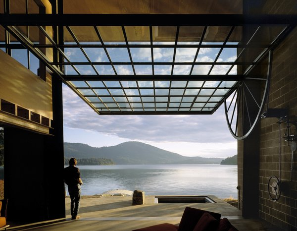 The defining feature of this lakeside cabin in northern Idaho is a 30-by-20-foot window wall that opens the living area to the surrounding lake and forest. Concrete blocks, steel, and plywood make up the simple palette of materials.