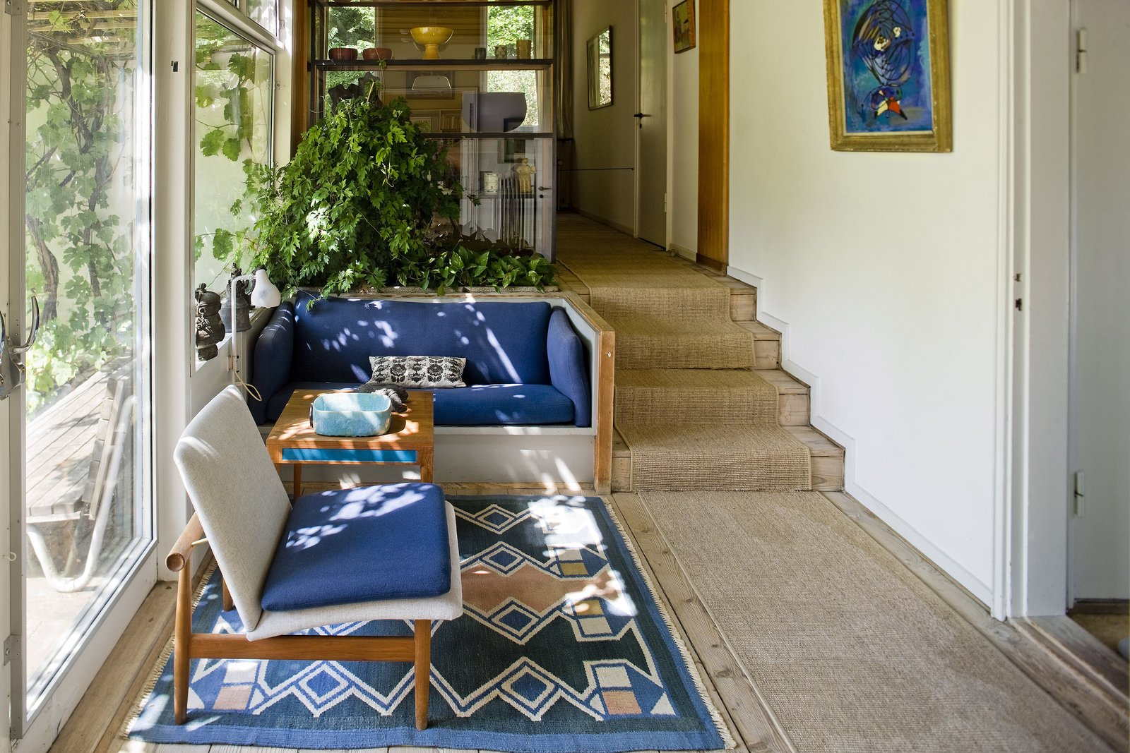 In the garden room, Juhl's 1957 Japanese chair lies next to a sofa table and a built-in bench, designed for the house. The blue upholstery matches Anna Thommsen's carpet. Tagged: Living Room, Sofa, Chair, and Rug Floor.  Photo 1 of 7 in The Highly Personal House of Danish Design Great Finn Juhl