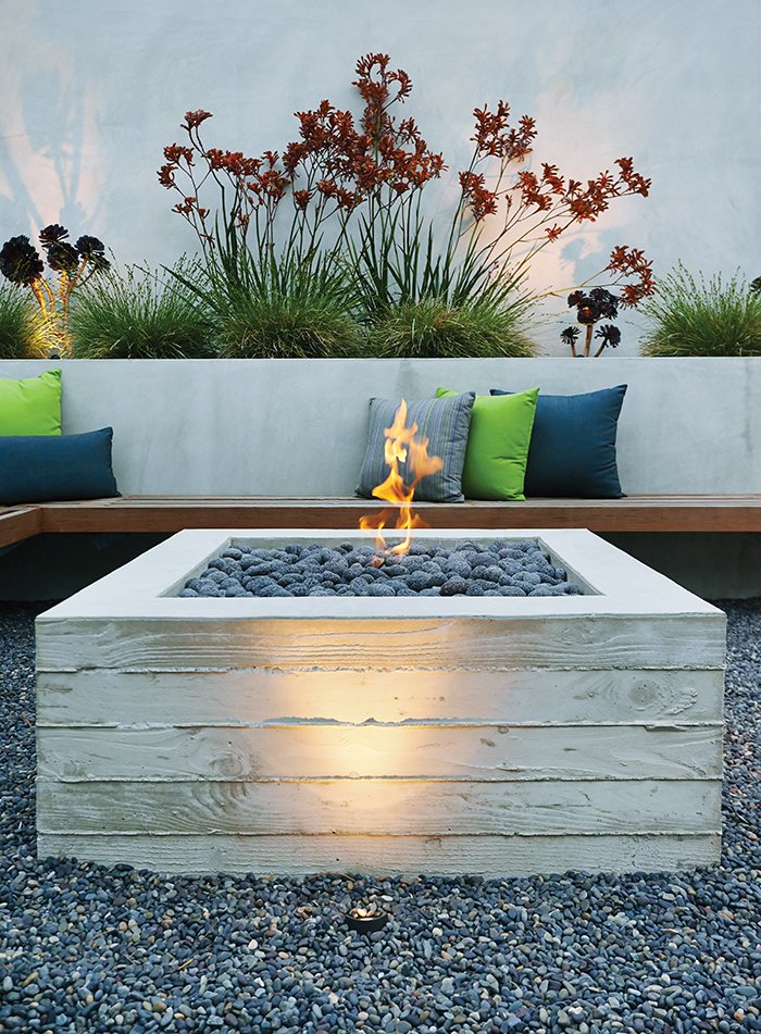 A cantilevered ipe bench hugs a custom board-formed concrete fire pit.  97+ Modern Fireplace Ideas by Dwell from A Craftsman-Style Bungalow is Turned Inside Out