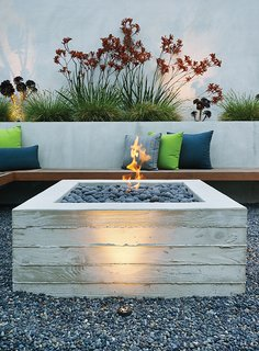 A Craftsman-Style Bungalow is Turned Inside Out - Photo 3 of 6 - A cantilevered ipe bench hugs a custom board-formed concrete fire pit.