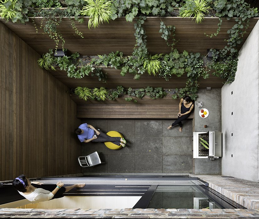 The dramatic 90-square-foot patio features a cooking and seating area. The floor and countertop are clad in Inca Gray Honed slate from Stone Source and the bench and planters are teak. By creating a vertical garden, Lubrano and Ciavarra integrated greenery into the views from every level of the house. Tagged: Outdoor, Small Patio, Porch, Deck, Concrete Patio, Porch, Deck, and Raised Planters.  Photo 5 of 7 in A Sophisticated Renovation of a 19th Century Manhattan Town House