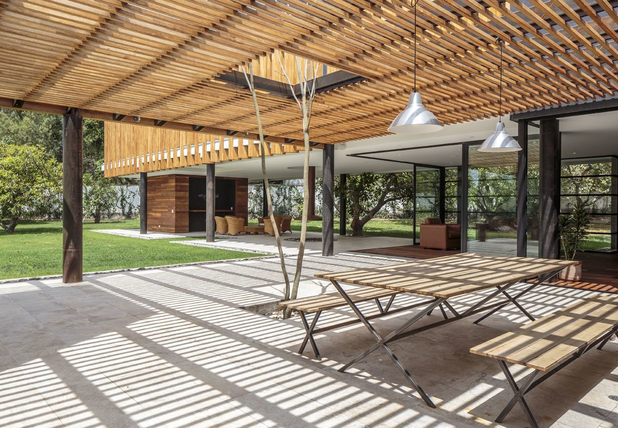 "Roberto Burneo designed this home for his eldest niece, her husband, and their three young children in a suburb outside Quito, the capital of Ecuador. The house is set on a flat expanse of land with fruit trees, and Burneo's design ""guides the social areas inward in order to link them to the gardens.""  Photo 5 of 9 in Longer Days Call For More Time on These 9 Modern Porches from Uncle Knows Best"