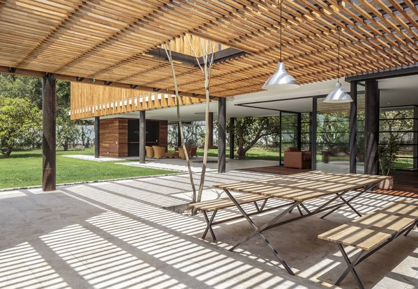 "Roberto Burneo designed this home for his eldest niece, her husband, and their three young children in a suburb outside Quito, the capital of Ecuador. The house is set on a flat expanse of land with fruit trees, and Burneo's design ""guides the social areas inward in order to link them to the gardens."""