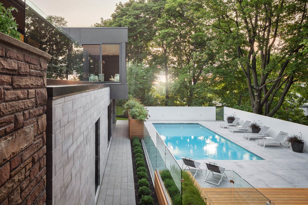 """The architects sited the patio and swimming pool beneath a canopy of mature maple trees, an element that they say makes the site """"an oasis in the heart of the city."""""""