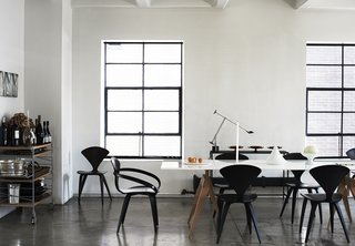 A Cherner Chair Retrospective - Photo 3 of 23 - Metal-framed windows stand out against the white walls in this loft. Black Cherner chairs and a white table continue the motif.