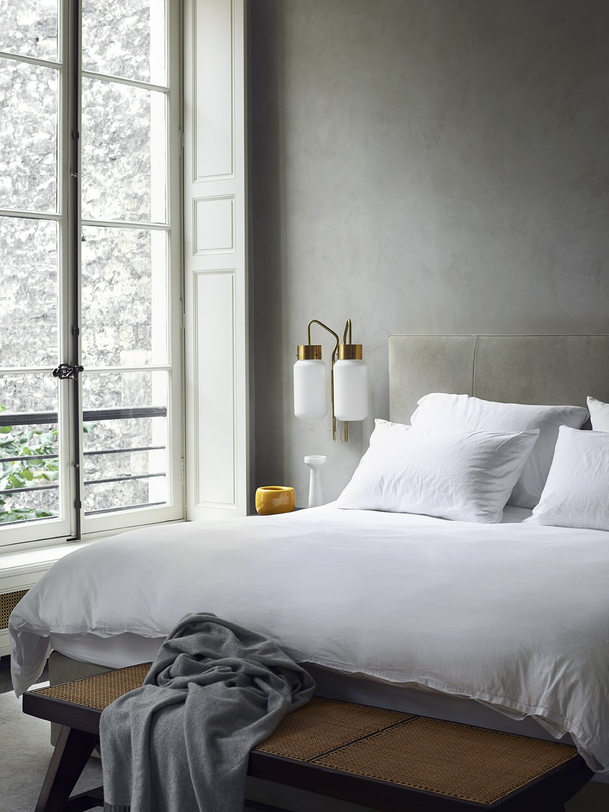 Architect Joseph Dirand's bedroom boasts sandy gray walls and upholstered headboard. The white bed linens help reflect daylight into the space and the Azucena sconces offer task illumination. Tagged: Bedroom, Bench, Bed, and Wall Lighting.  Monochromatic Color Palettes Are the Ultimate Modern Design Tool by Diana Budds