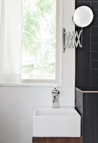 In the bathroom, a chrome waterfall faucet by LightInTheBox tops a 12.6-inch-square Mini Nova basin by Barclay; a retractable Ikea mirror is the only concession to vanity.