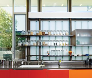 This House Doesn't Hold Back on Colorful Details - Photo 6 of 11 - The red- and orange-painted cabinets are meant to reflect sunlight and represent the heart of the home. The glass-fronted cabinets in the kitchen are by Henrybuilt, and the clear containers with dry goods are from the Container Store.