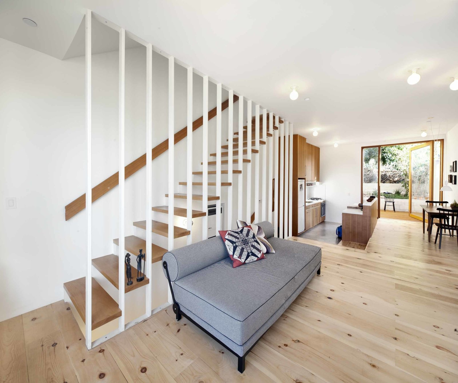 """The first floor contains the living room and kitchen, which opens out onto a petite back garden and an avocado tree. The kitchen is slightly sunken and has a polished concrete floor, which subtly demarcates it from the rest of the space. Materials in the kitchen set the home's material palette, with vertical Douglas fir cabinets and the same 3"""" x 6"""" subway tiles that appear in the bathroom for the backsplash. The Fisher & Paykel dishwasher is hidden inside the island: """"I wanted the island to look more like a credenza or piece of furniture,"""" says Storey.  The wood floor boards in the living room are white pine, a soft wood Storey chose for its knotty look. """"The wood dries a lot over time, so small gaps have opened up between them. Because it's such a simple white space, it's nice to have that rough warmth and character in the floors."""""""