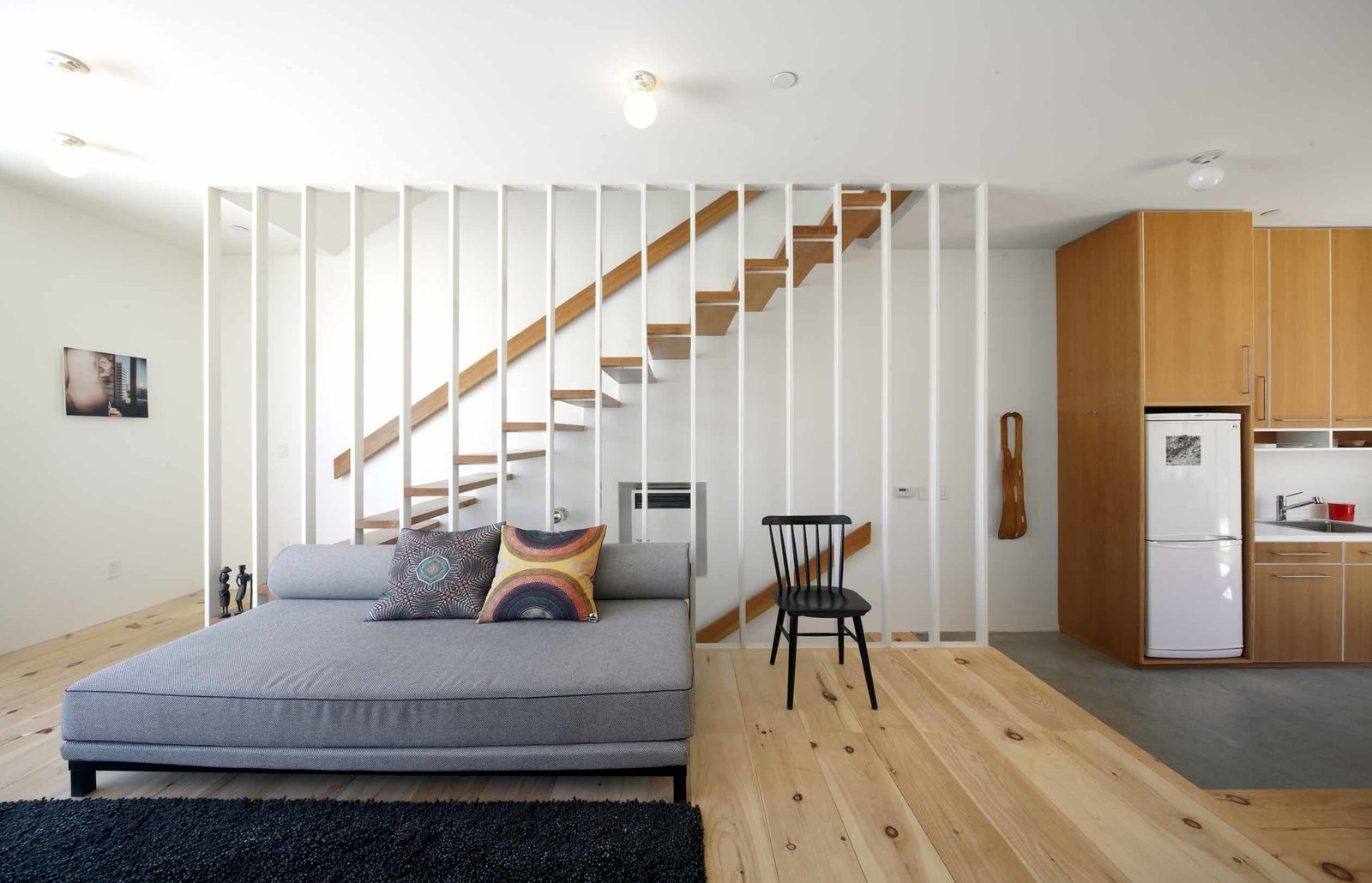 """""""My number one concern was to make it feel like a normal house [despite its restricted layout],"""" says Storey. """"You're stuck with a box, and if you want to get creative with that, it's only going to make it a smaller box. Even the stairwell, which filters light into the core of the house, is a chunk of space I've taken away from it. It's unusual how small the house looks on the outside compared to how big it feels inside.""""  Photo 3 of 9 in Home and Studio Maximizes Very Narrow Site in Echo Park"""