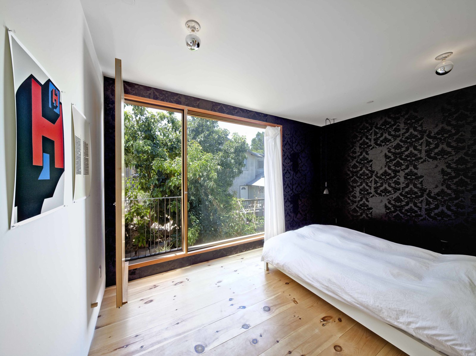 """The second story has two rooms and a bathroom. Storey uses the room overlooking the street as his architecture studio, and the quiet back room as a bedroom. Its small balcony is the height of the avocado tree canopy, giving him the sense that he sleeps in a tree.   The wallpaper is the architect's own design. """"The wallpaper is called Torn and Confused,"""" he says. """"It was originally designed to look like it was torn from the wall, exposing another layer of wallpaper underneath. I love the irony of using it on a new house."""" Home and Studio Maximizes Very Narrow Site in Echo Park - Photo 6 of 9"""