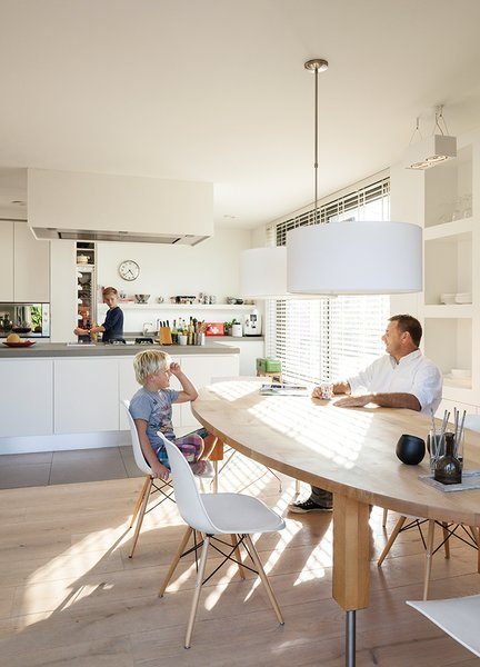 """The kitchen of a home on an Amsterdam canal """"is where it all happens,"""" says Van Zeijl. As the hub of the home, the room is situated at the front of the house and features a minimal palette and Belgian granite countertops. The table is by Pilat & Pilat and the pendants are from It's About Romi."""