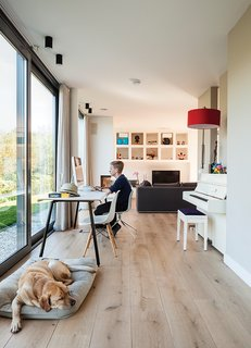 "A Modern Take on the Pitched-Roof - Photo 7 of 12 - Bram sits at a table by Gispen in the oak-floored public side of the house, facing the water, while the dog, Bommel, relaxes nearby. ""We really like the indoor-outdoor effect,"" says Bram's dad, Mark de Graaf. ""The ground floor opens on three sides—on a summer day, it stays cool."""